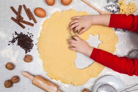 Child cuts out cookies from dough