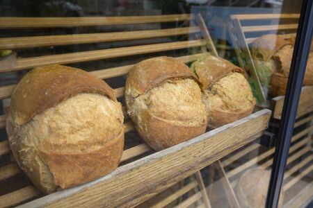 Showcase shelf with round breads in bakery. Closeup