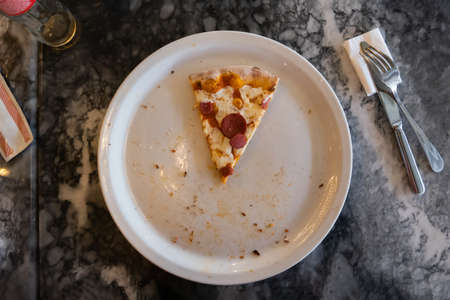 1 slice of pizza in a white plate