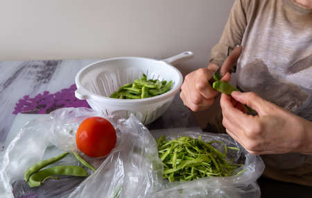 green beans Woman cooking in the kitchen at home Фото со стока