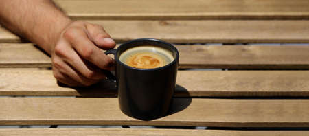 hand holding coffee cup on wooden table