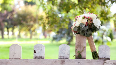 bridal bouquet on wooden fence, front view