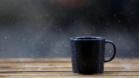 black coffee mug standing on wooden floor in rainy weather