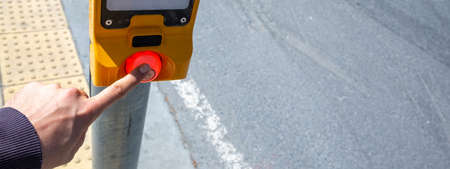 Hand pressing a button at traffic lights Фото со стока