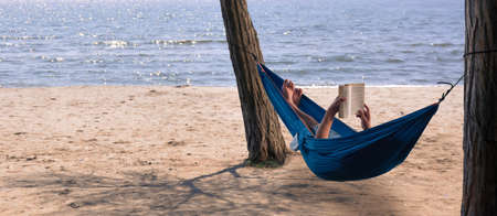 man reading a book in a hammock by the sea