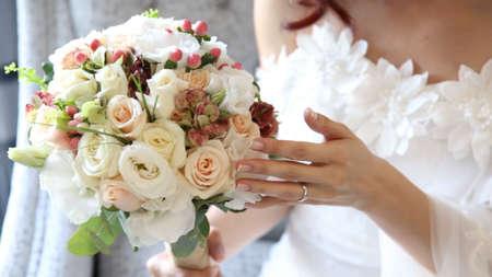 bride holding flower bouquet, close up