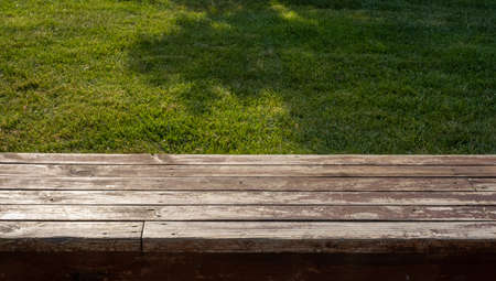 empty wooden floor in front of grass background Фото со стока