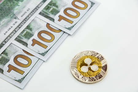 Ripple coin and 100 dollars bills on a white background