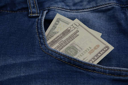 Blue jeans pocket with 20 dollars banknotes