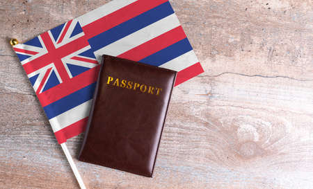 Passport and a Hawaii flag on a wooden background. Travel concept
