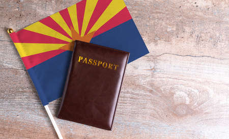 Passport and a Arizona flag on a wooden background. Travel concept