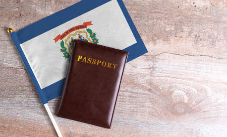 Passport and a West Virginia flag on a wooden background. Travel concept