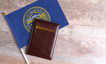 Passport and a Nebraska flag on a wooden background. Travel concept