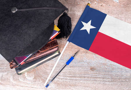 Black graduation hat on books next to Texas flag, education concept, top view Stock Photo