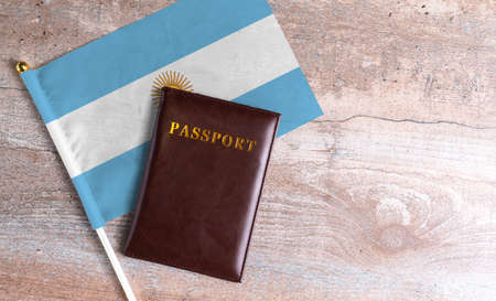 Passport and a Argentina flag on a wooden background. Travel concept