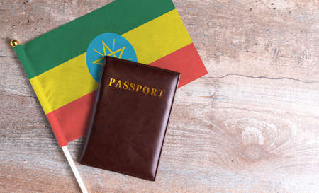 Passport and a Ethiopia flag on a wooden background. Travel concept