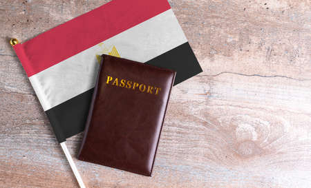 Passport and a Egypt flag on a wooden background. Travel concept