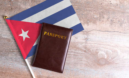 Passport and a Cuba flag on a wooden background. Travel concept
