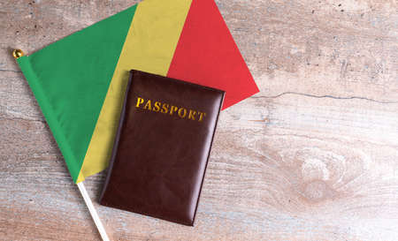 Passport and a Congo republic flag on a wooden background. Travel concept