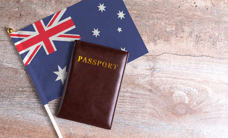 Passport and a Australia flag on a wooden background. Travel concept
