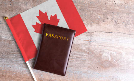 Passport and a Canada flag on a wooden background. Travel concept