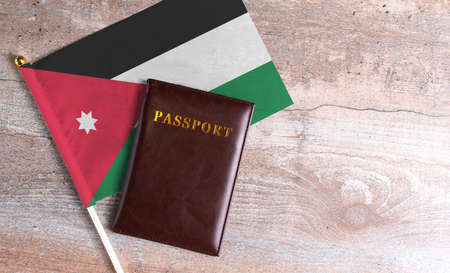 Passport and a Jordan flag on a wooden background. Travel concept