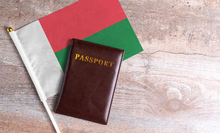 Passport and a Madagascar flag on a wooden background. Travel concept