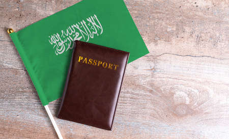 Passport and a Saudi Arabia flag on a wooden background. Travel concept