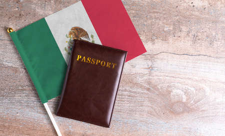 Passport and a Mexico flag on a wooden background. Travel concept