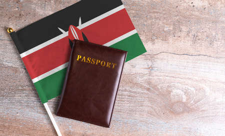 Passport and a Kenya flag on a wooden background. Travel concept