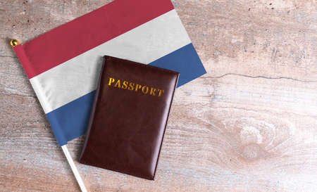 Passport and a Netherlands flag on a wooden background. Travel concept
