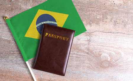 Passport and a Brazil flag on a wooden background. Travel concept