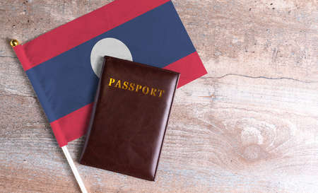 Passport and a Laos flag on a wooden background. Travel concept
