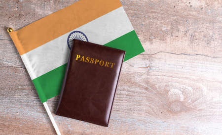 Passport and a India flag on a wooden background. Travel concept