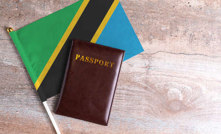 Passport and a Tanzania flag on a wooden background. Travel concept