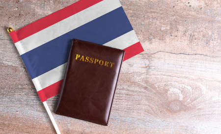Passport and a Thailand flag on a wooden background. Travel concept