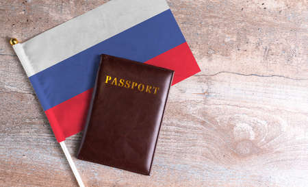 Passport and a Russia flag on a wooden background. Travel concept