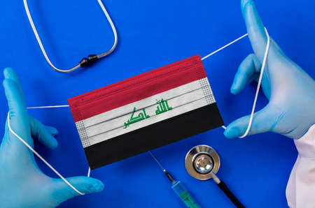 Medical mask with the flag of Iraq in the hands of a doctor and stethoscope, flat lay. pandemic