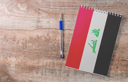 Notepad with Iraq flag, pen on wooden background, study concept