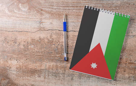 Notepad with Jordan flag, pen on wooden background, study concept 写真素材
