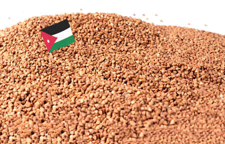 Jordan flag sticking in buckwheat grain. The concept of export and import of buckwheat