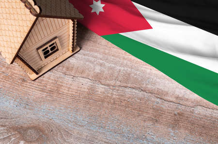 House model near Jordan flag. Real estate sale and purchase concept. Space for text.