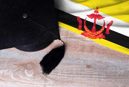 Black graduation hat on Brunei flag, education concept, top view Stock fotó