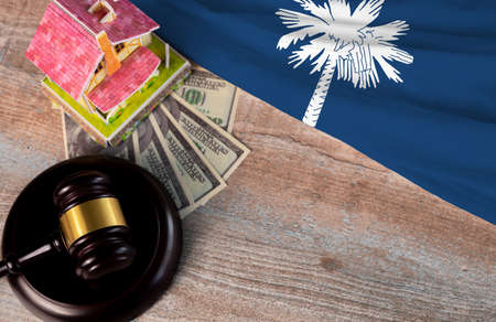 Property auction, flag South Carolina, gavel wooden and model house on wooden background, lawyer of home real estate
