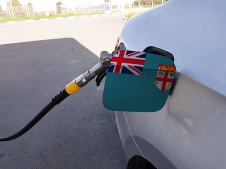 Flag of Fiji on the car's fuel tank filler flap. Petrol station. Fueling car at a gas station. Stock Photo