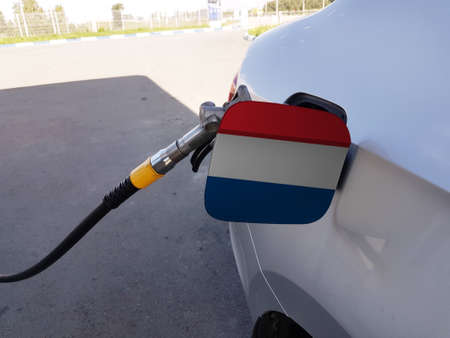 Flag of Netherlands on the car's fuel tank filler flap. Petrol station. Fueling car at a gas station.