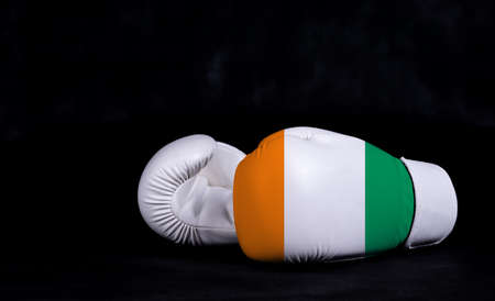 Boxing glove with Code d Ivoire flag on black background
