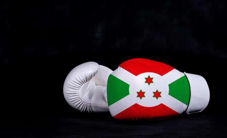 Boxing glove with Burundi flag on black background