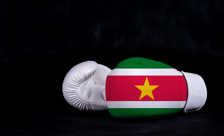 Boxing glove with Suriname flag on black background