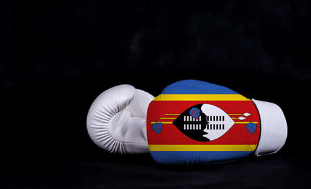 Boxing glove with Swaziland flag on black background Фото со стока